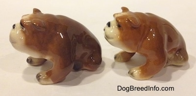 The left side of two brown with white miniature Bulldogs that are in a sitting pose. The figurines are glossy.