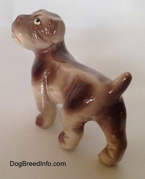 The back left side of a brown and white ceramic Bulldog figurine. The figurines tail is arched up.