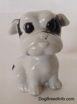 A white with black bone china Bulldog figurine. The figurine has detailed black circles for eyes.