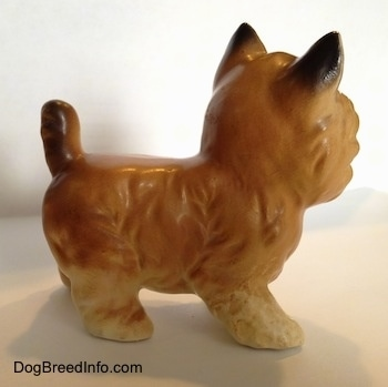 The right side of a tan with black Cairn Terrier figurine. The back of the figurines ears are black.