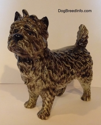 The front left side of a black and white Cairn Terrier figurine. The eyes of the figurine are black circles.