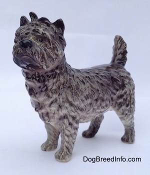 The front left side of a gray and white Cairn Terrier figurine. The figurine has black circles for eyes, a wavy textured coat, a tail that is up in the air and small perk ears.
