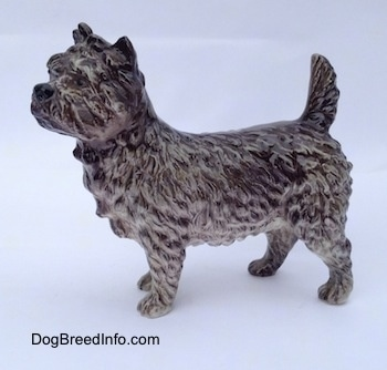 The left side of a gray and white Cairn Terrier. The tail of the figurine is arched up.