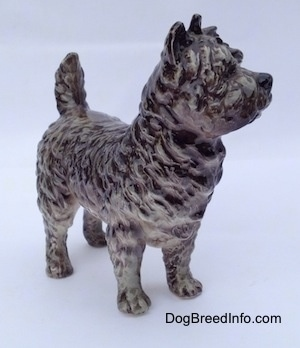 The front right side of a gray and white Cairn Terrier figurine. The figurine is very detailed.