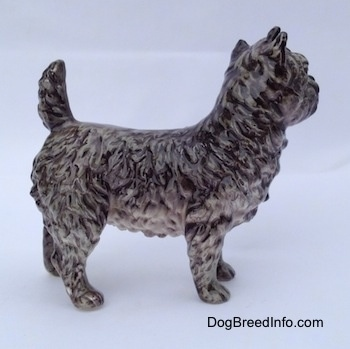 The right side of a gray and white Cairn Terrier figurine. The figurine has fine paw details as the fur coat.