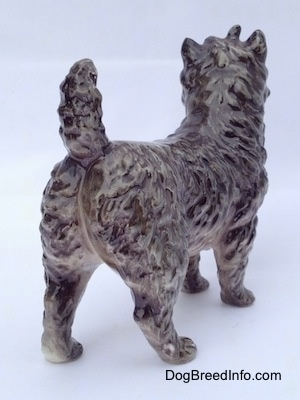 The back right side of a gray and white Cairn Terrier figurine. The figurines tail is arched up.