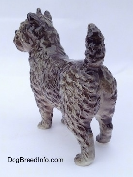 The back left side of a gray and white Cairn Terrier figurine. The figurine has fine hair details.