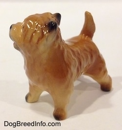 The front left side of a brown with black Cairn Terrier figurine. The paws of the figurine are black.