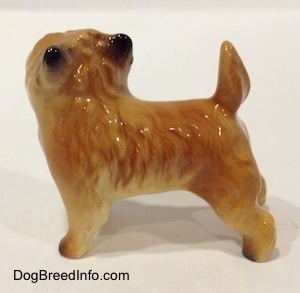 The left side of a brown with black Cairn Terrier figurine. The figurine has fine hair details, a tail that is up in the air and small black perk ears. Its body is tan.