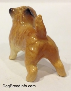 The back left side of a brown with black Cairn Terrier figurine. The figurine has a tail that is in the air.