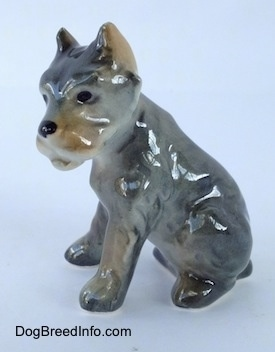 The left side of a grey with black and tan Cane Corso Italiano puppy figurine. The figurine is glossy.