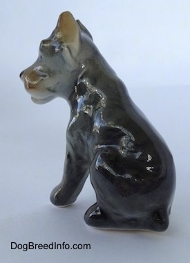 The back left side of a grey with black and tan Cane Corso Italiano puppy figurine. The figurine lacks fine detail.