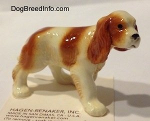 The front right side of a red and white Cavalier King Charles Spaniel figurine. The figurine has black circles for eyes.