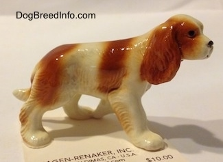 The right side of a red and white Cavalier King Charles Spaniel figurine. The figurine has fine hair details.