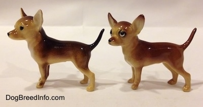 The left side of two Chihuahua ceramic figurines that look different. The left most figurine has black circles for eyes.