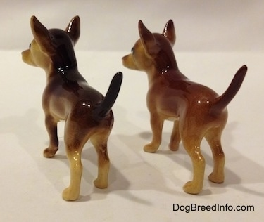 The back right side of two different ceramic Chihuahua figurines. The figurines have large ears and long tails.