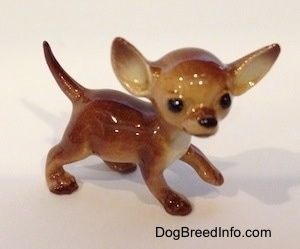 The right side of a brown with tan ceramic Chihuahua dog figurine. The dog has black circles for eyes.