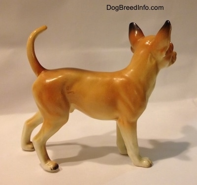 The right side of a porcelain tan with white Chihuahua figurine. The figurine has black tips for ears.