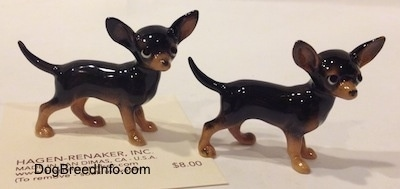 The right side of two different black with tan Chihuahua figurines. The figurines are glossy.