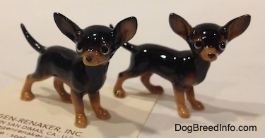 Two black with tan Chihuahua figurines that look different. The feet of the figurines are tan.