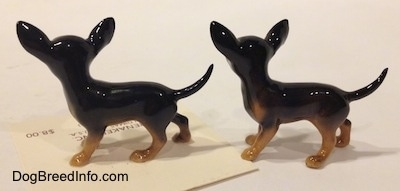 The left side of two slightly different black with tan Chihuahua figurines. The figurines have long tails.