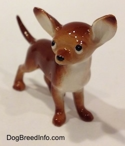 A brown with white Chihuahua figurine. The figurine has a black circle for a nose.