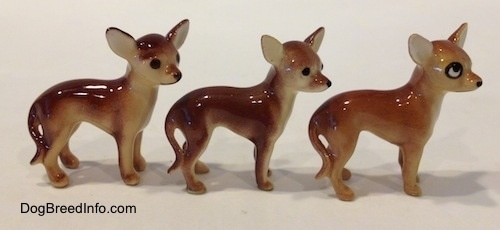 The right side of three different ceramic Chihuahua figurines. The back two figurines have black circles for eyes and a nose.