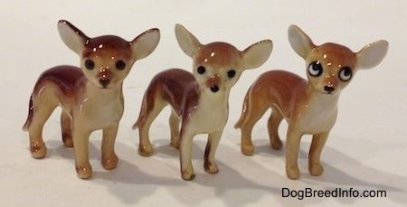 Three Chihuahua ceramic figurines that are the same but painted differently. They have round heads, black noses and large ears that are set wide apart and stick out to the sides.