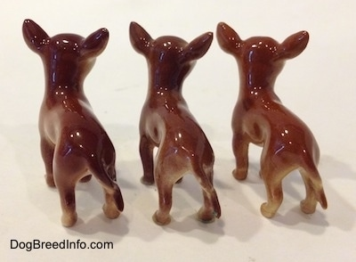 The back of three different ceramic Chihuahua figurines. The figurines have long tails.