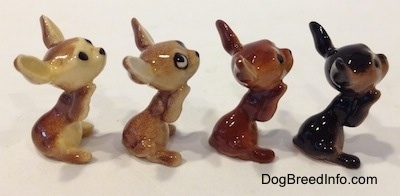The right side of four variations of a Chihuahua figurines that is in a begging position. The figurines are glossy.