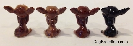 The back of four different Chihuahua figurines in a begging position. The figurines do not have tails.