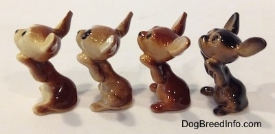 The left side of four different Chihuahua figurines that are in a begging position. The figurines are glossy.