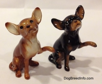 Two different Chihuahua figurines that have one paw in the air. The figurines are glossy.