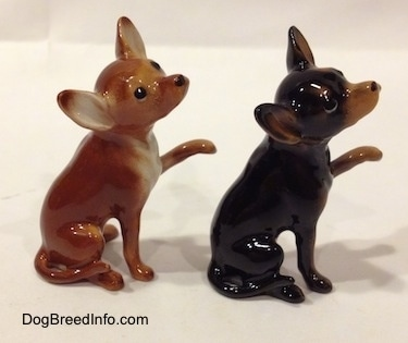 The right side of two different looking Chihuahua figurines that have one paw in the air. The figurines have long tails.