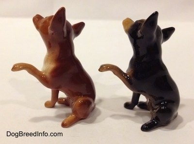 The left side of two Chihuahua figurines that are different and also have one paw in the air.