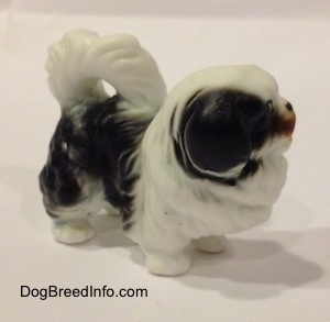 The front right side of a black and white bone china Japanese Chin dog figurine. The ears of the figurine are hard to differentiate from the head.