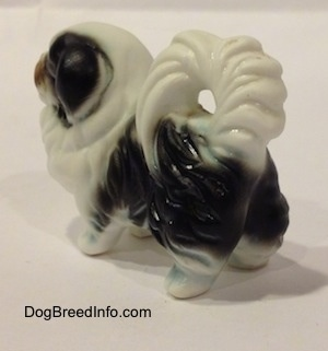The back left side of a white and black bone china Japanese Chin dog figurine. The figurine has great hair details.