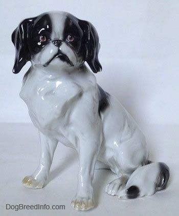 A white with black vintage Goebel double-crown mark Japanese Chin dog figurine. The figurine has great hair details.