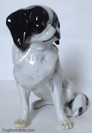 The front of a white with black Japanese Chin dog figurine. The figurine has yellow nails at the top of its paws.