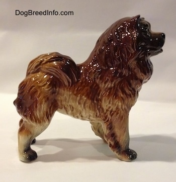 The right side of a porcelain brown with black Chow Chow figurine that has a black face.