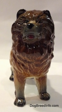 A porcelain brown with black Chow Chow figurine. The figurine has small black circles for eyes.