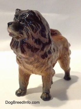 The front left side of a brown with black Chow Chow figurine. The figurine has very few details in its face. The dog has a big head, thick body and a black nose.