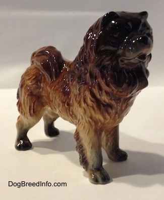 The front right side of a brown with black Chow Chow figurine. The figurine has a black face.
