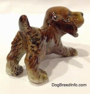 The back right side of a brown and tan Cocker Spaniel puppy figurine. The figurine has detailed hair brushings.