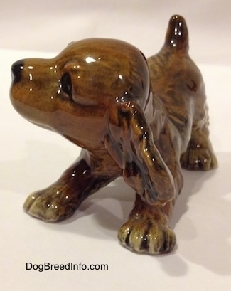 The front left side of a brown and tan Cocker Spaniel puppy figurine. The figurine is designed to look like it is bowing.
