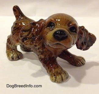 A brown and tan Cocker Spaniel puppy figurine is standing across a beige backdrop and it is looking forward.