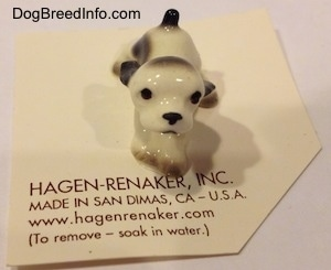 A white with black ceramic Cocker Spaniel puppy figurine.