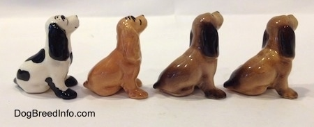 The right side of four color variations of a Cocker Spaniel figurine. All of the figurines are glossy.