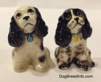 Two different ceramic Cocker Spaniel figurines. Are looking up and there heads are tilted to the left. The figurine on the left has light eye details and the right figurine has fine eye details. The dogs have black noses and black lips. One dog has a blue dog tag and the other has a yellow dog tag.