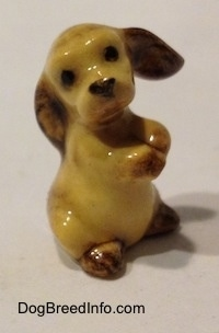 The right side of a tan with brown ceramic Cocker Spaniel puppy figurine. It has black circles for eyes.